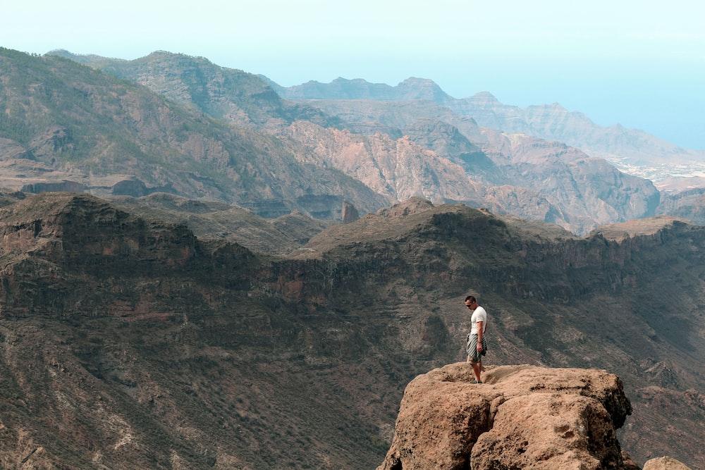man in white shirt standing on brown rock mountain during daytime