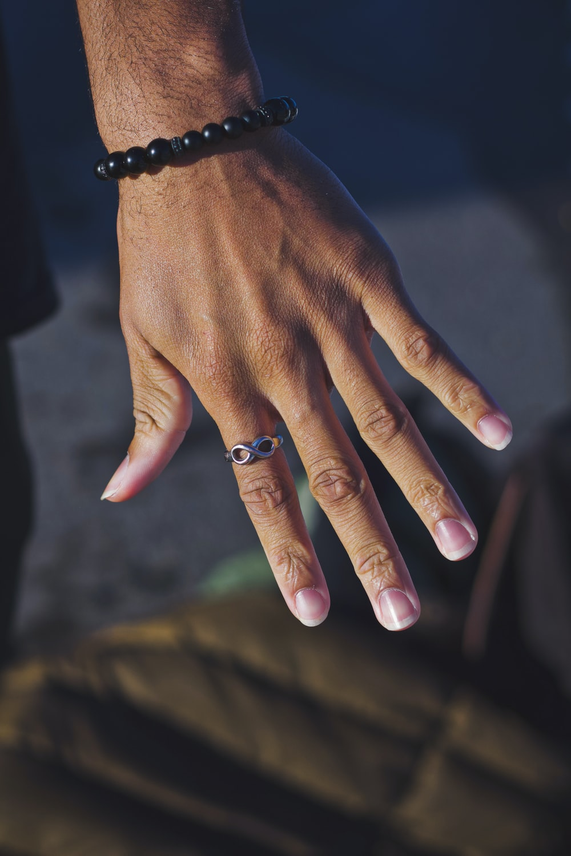 person wearing black beaded bracelet