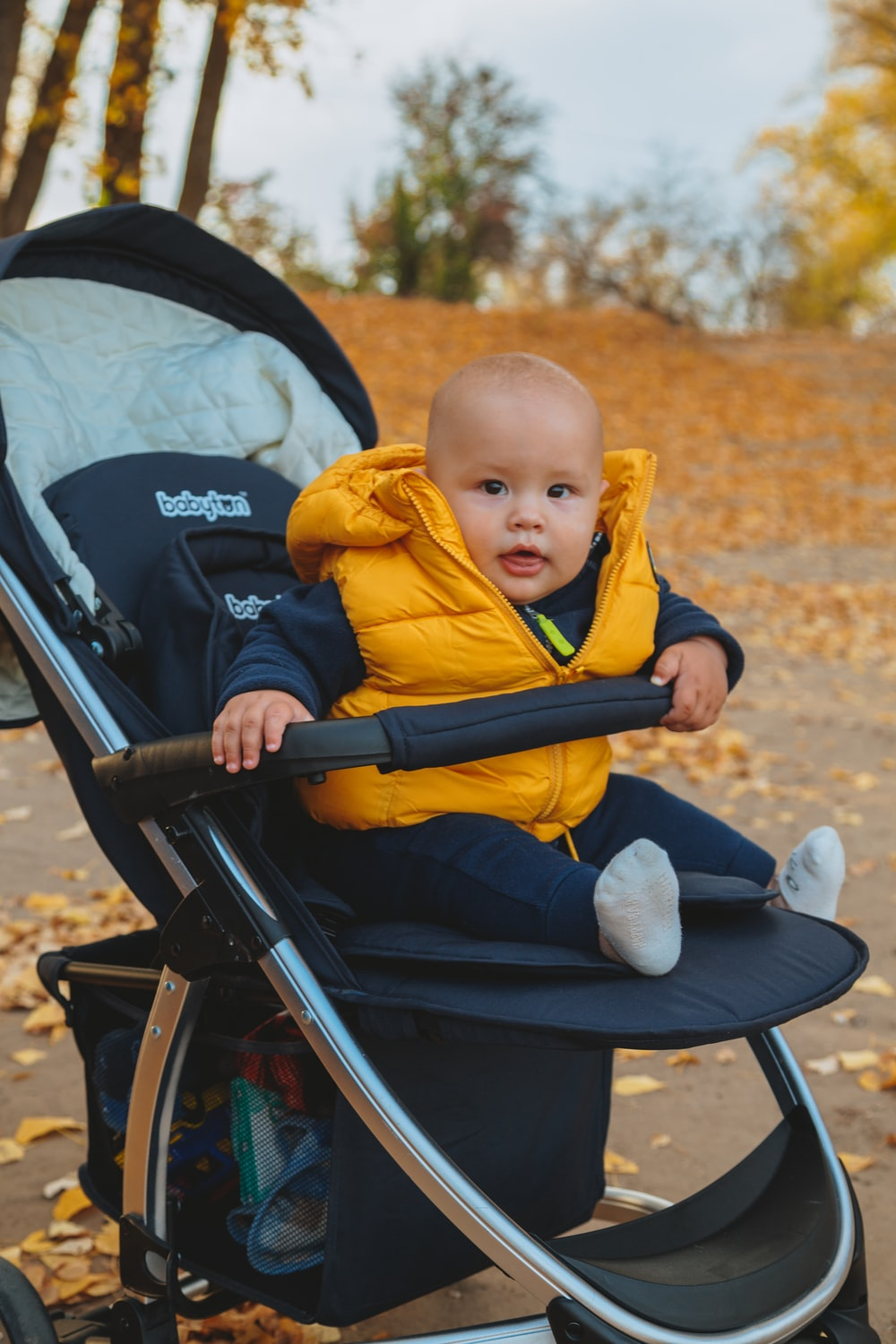 child in yellow hoodie sitting on stroller