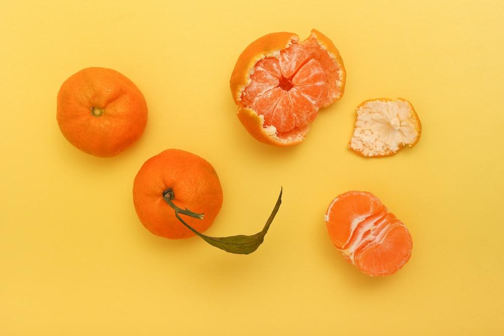 sliced orange fruit beside white garlic and garlic
