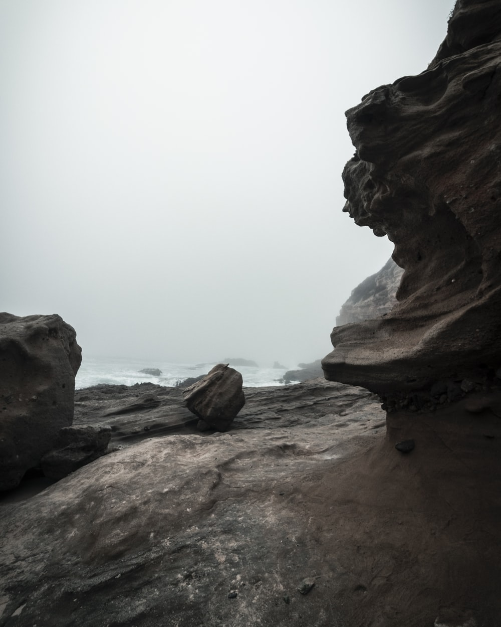 brown rock formation near body of water during daytime