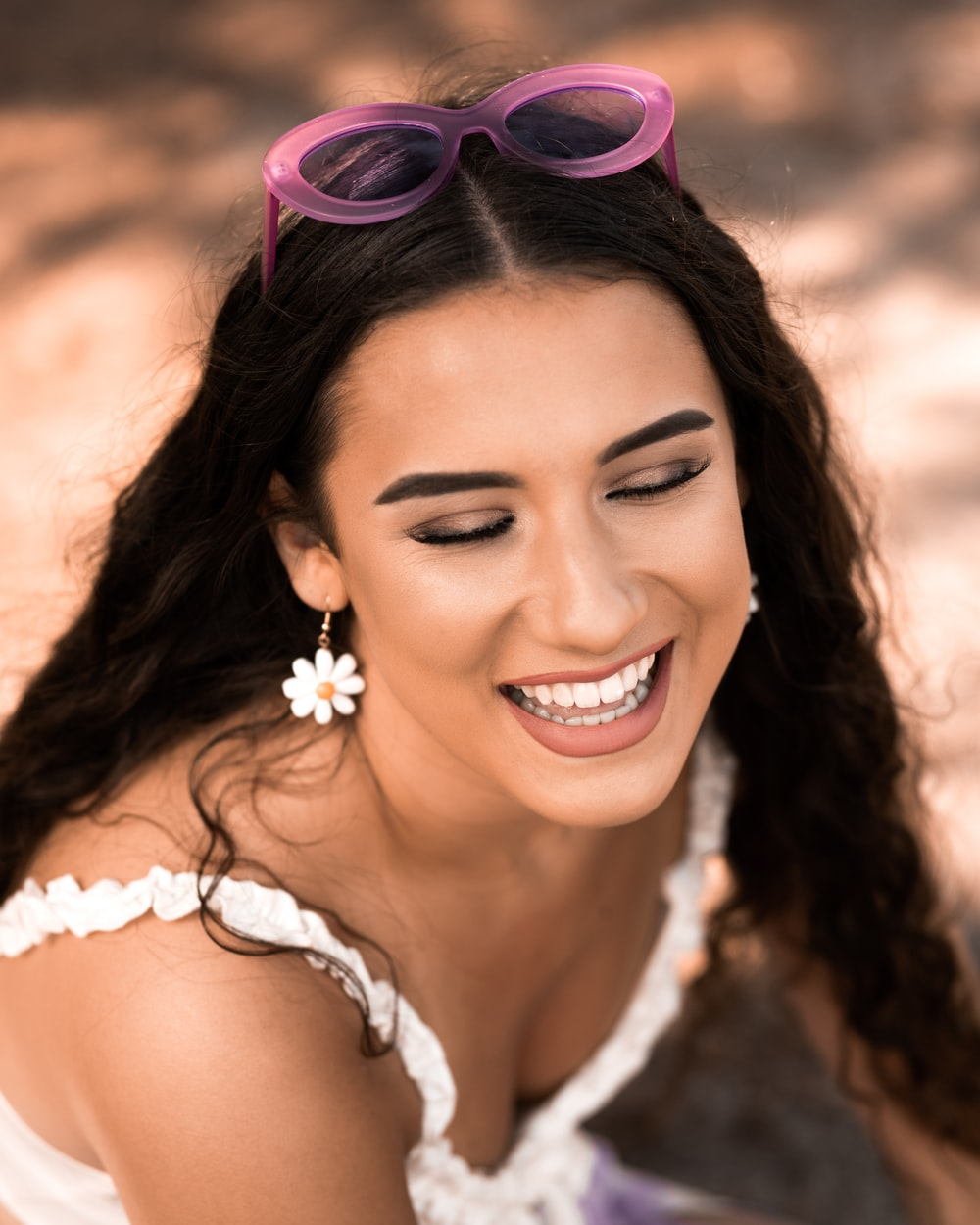 smiling woman wearing white floral headband and white floral sleeveless top