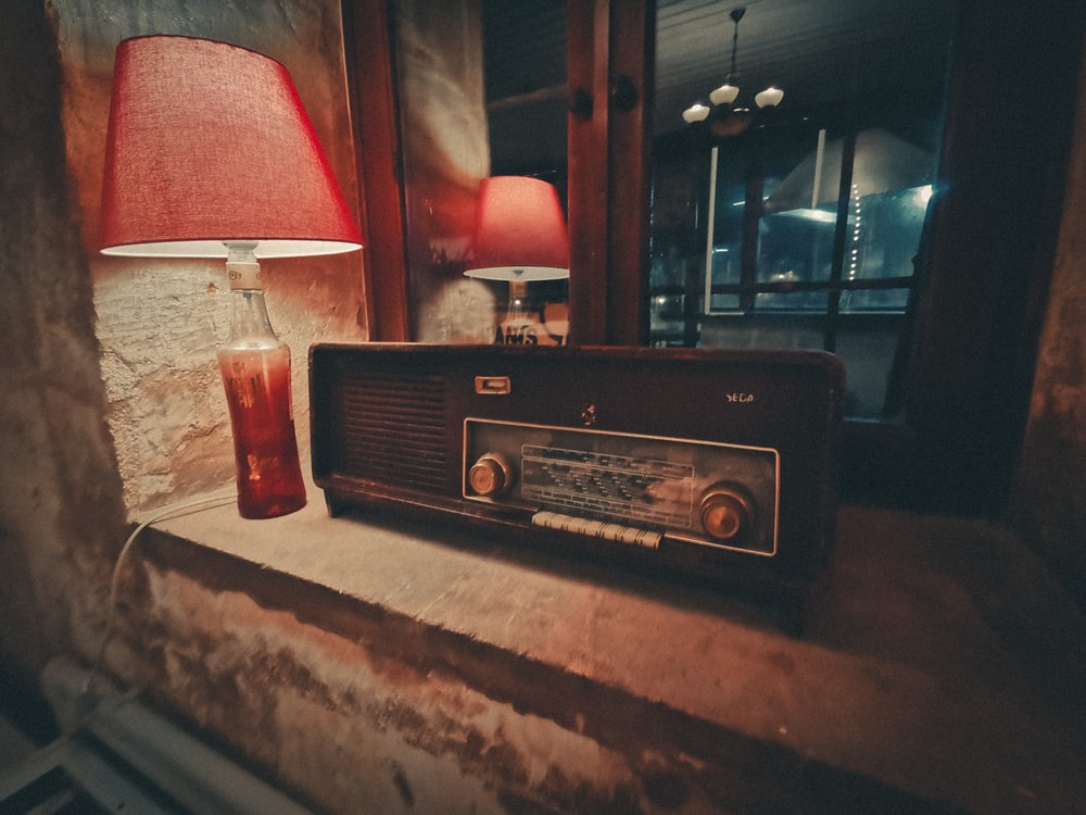 black and red radio on brown wooden table