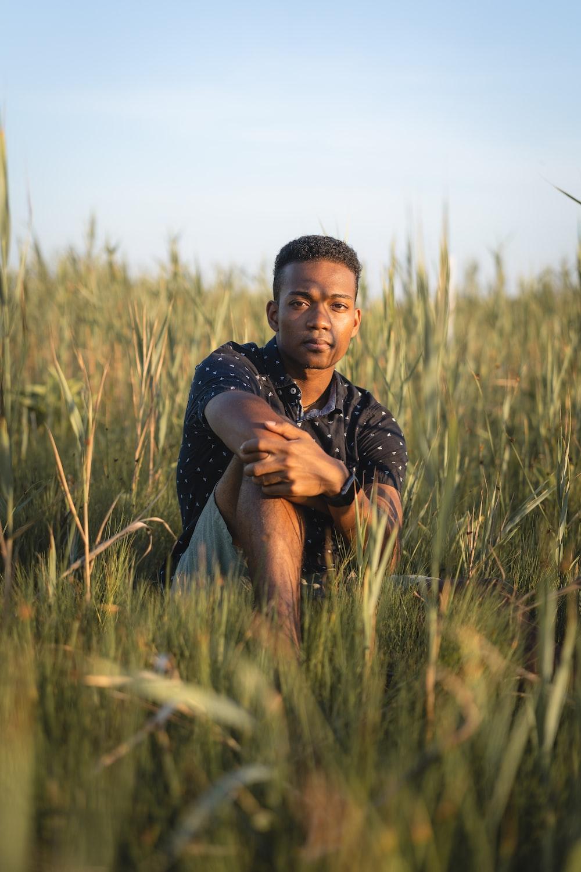 man in black shirt sitting on green grass field