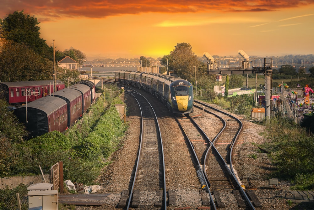 yellow and black train on rail tracks during sunset
