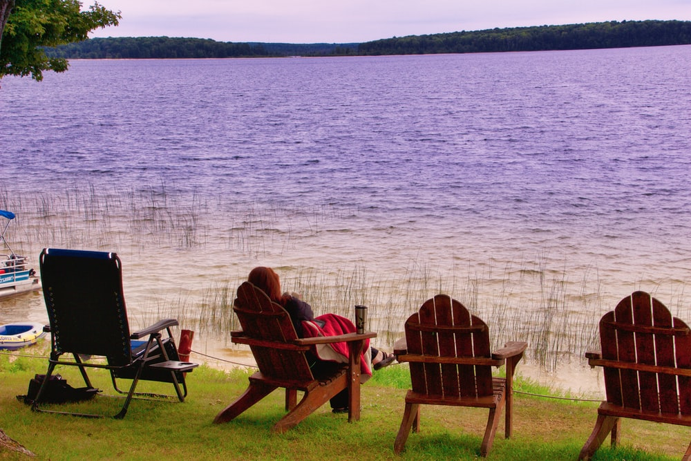 2 person sitting on brown wooden chair near body of water during daytime