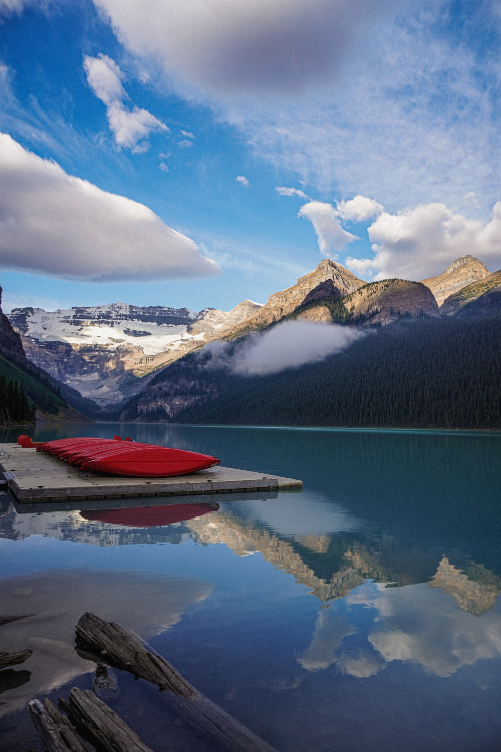 red boat on lake near snow covered mountain under blue sky and white clouds during daytime
