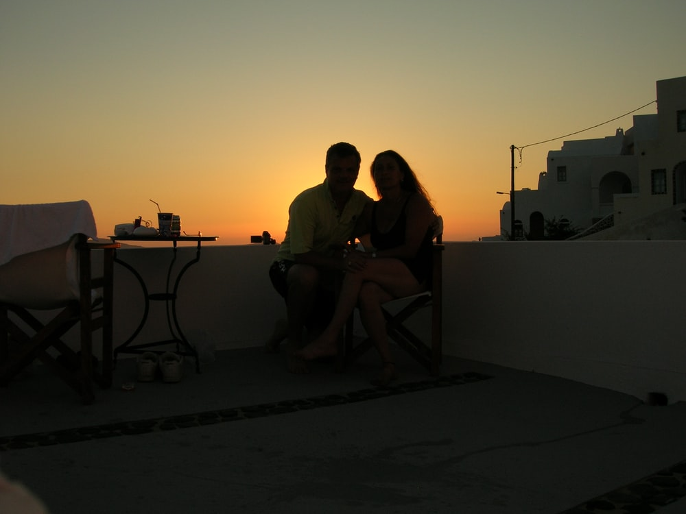 man and woman sitting on chair during sunset