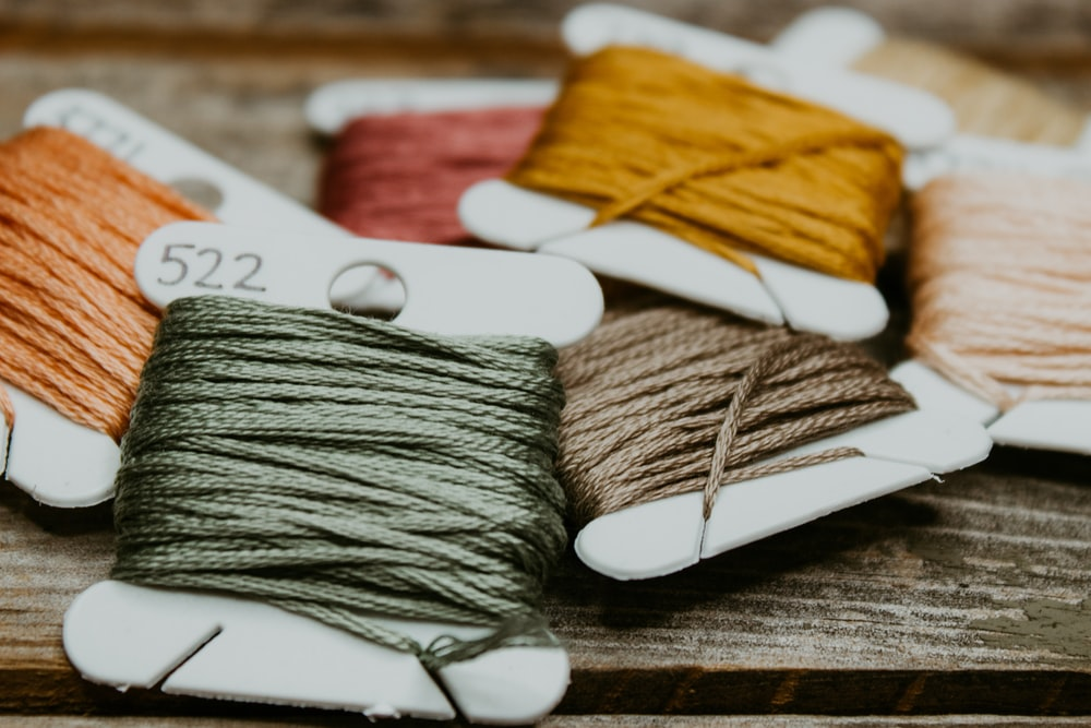 green and yellow yarn on brown wooden table