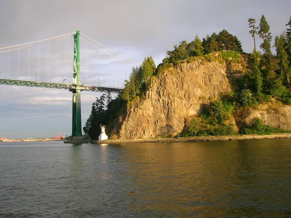 bridge over river near mountain during daytime