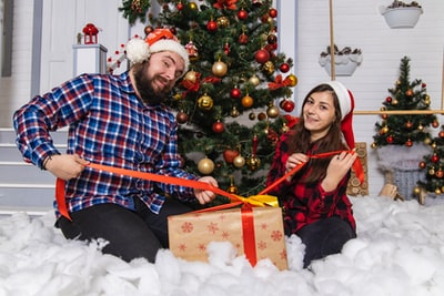 man and woman sitting on white snow christmas eve zoom background