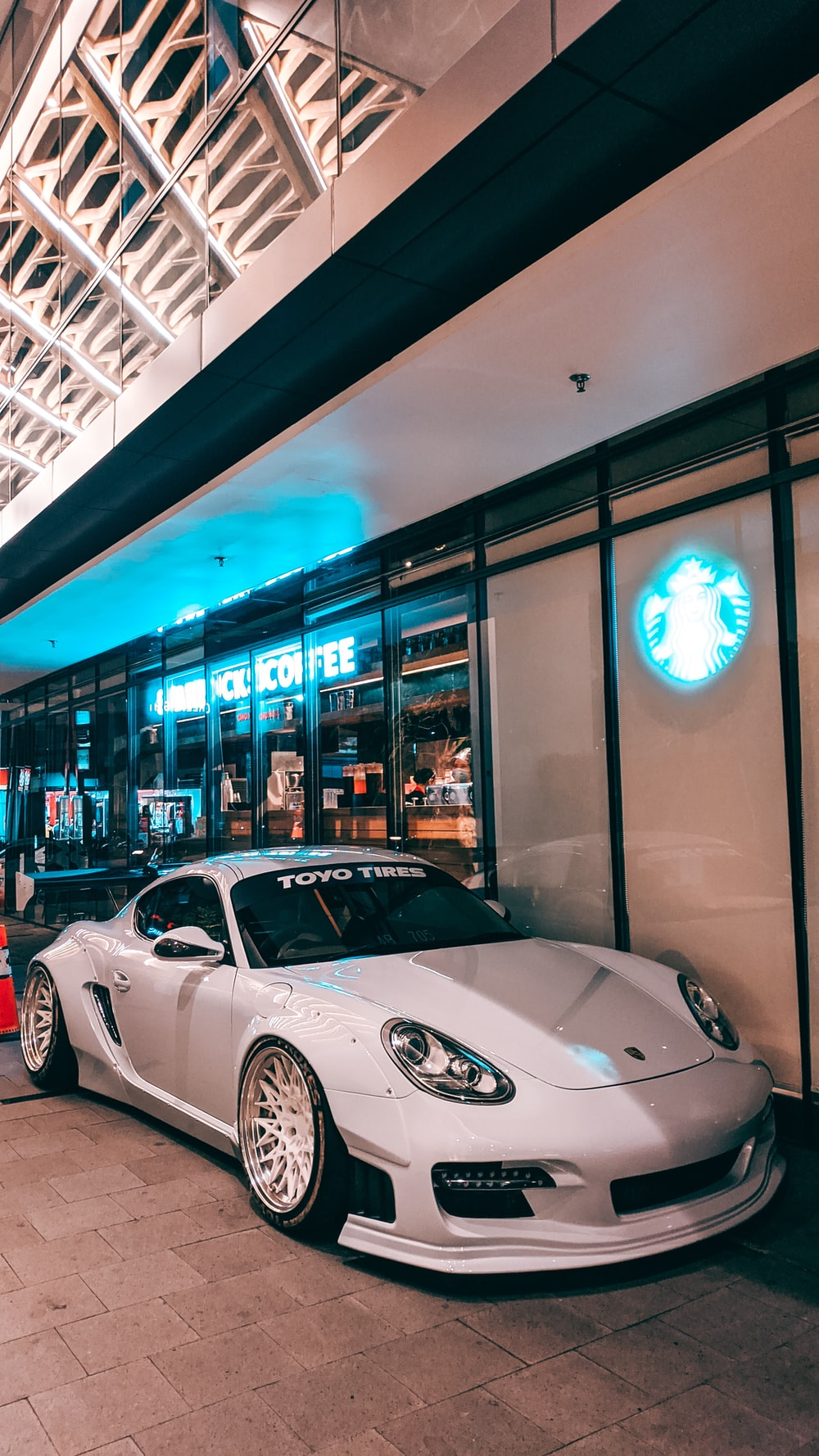 white porsche 911 parked in front of store