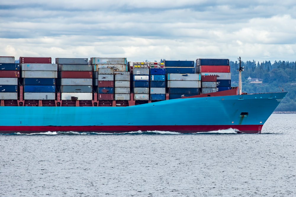 red and blue cargo ship on sea during daytime
