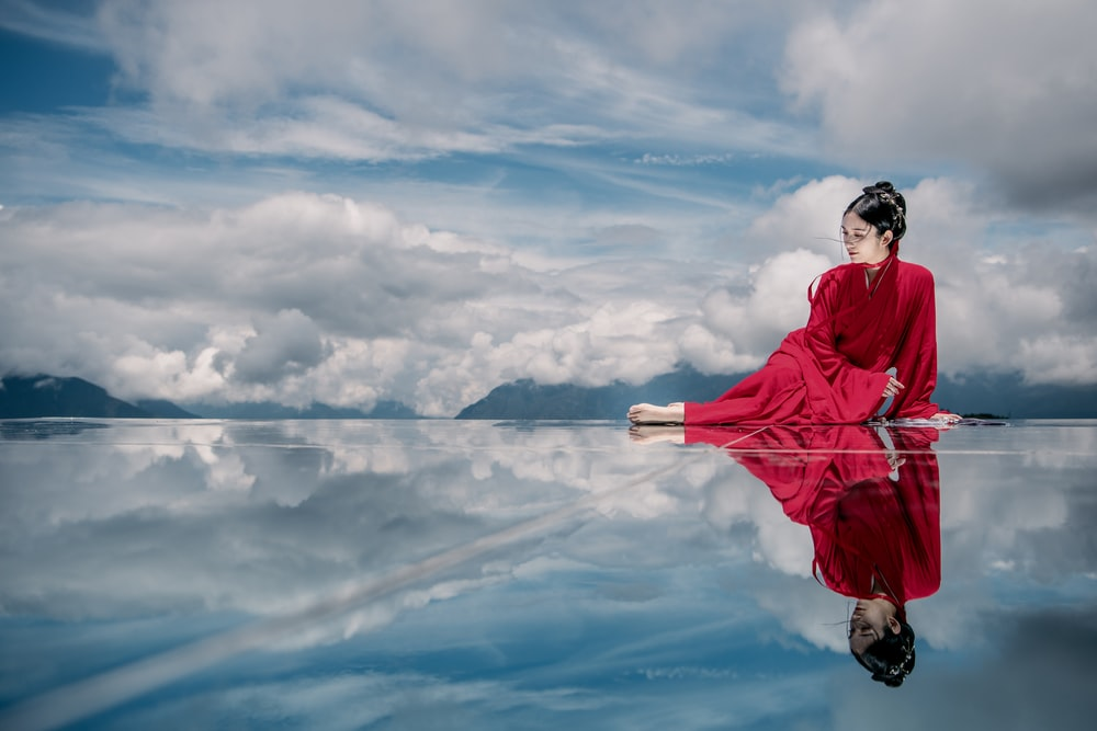 woman in red jacket and black pants standing on rock under white clouds and blue sky