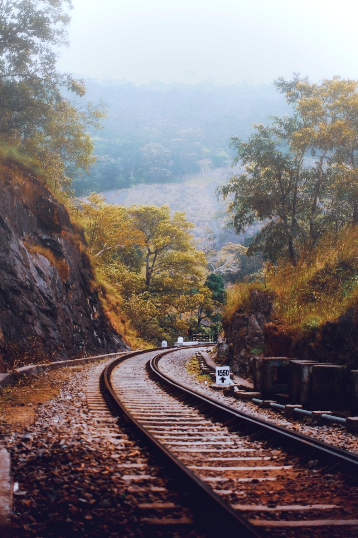 train rail near green trees during daytime