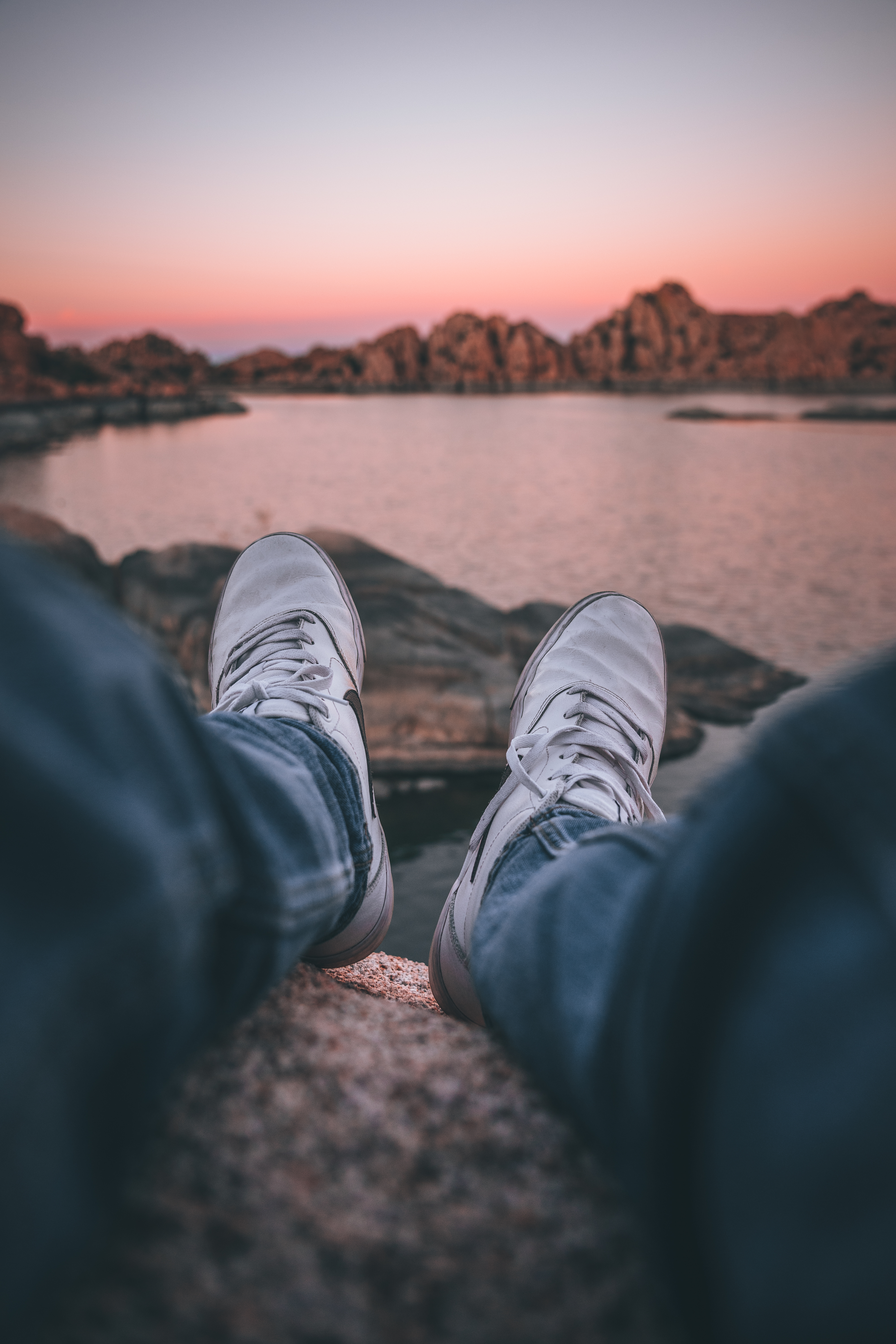 person-in-blue-denim-jeans-and-gray-sneakers-sitting-on-rock-near-body-of-water-during