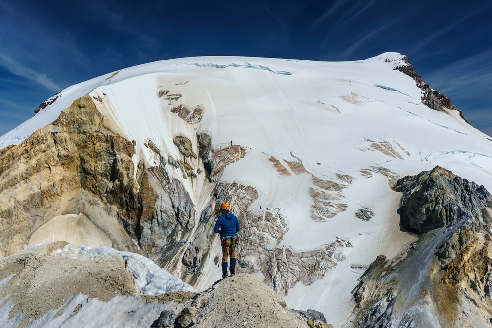man in blue jacket and black pants standing on snow covered mountain during daytime
