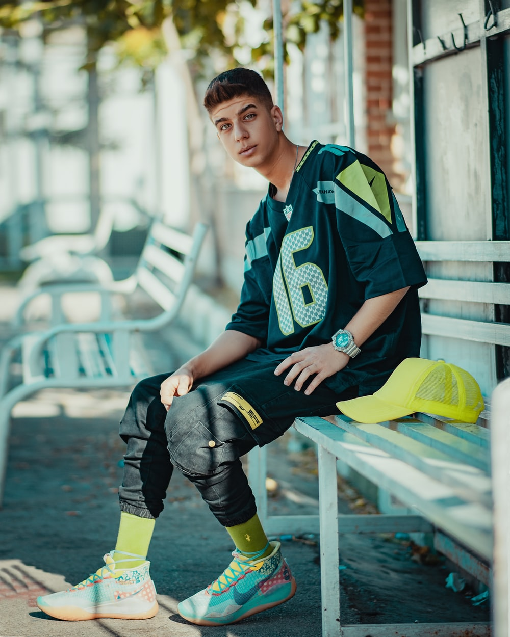 boy in green and white camouflage jacket sitting on yellow plastic chair