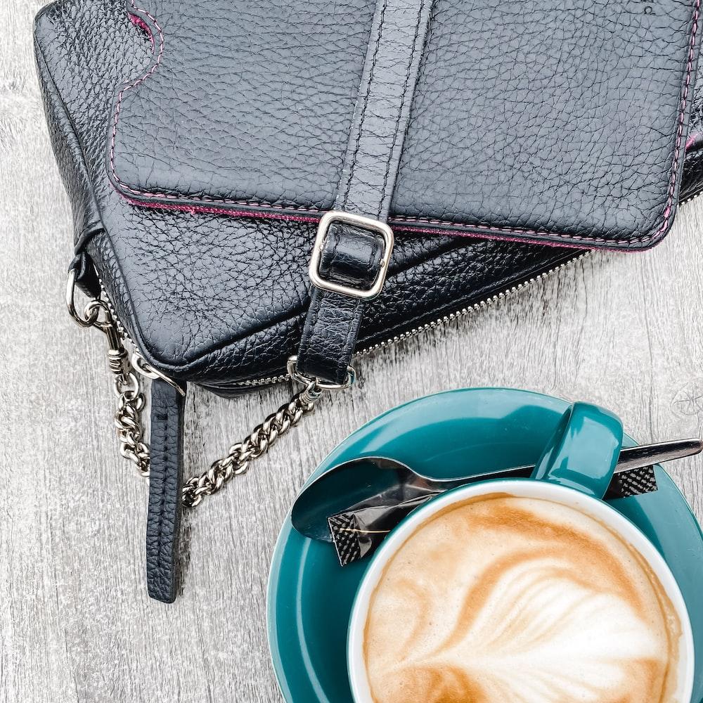 black leather sling bag beside blue ceramic mug with coffee