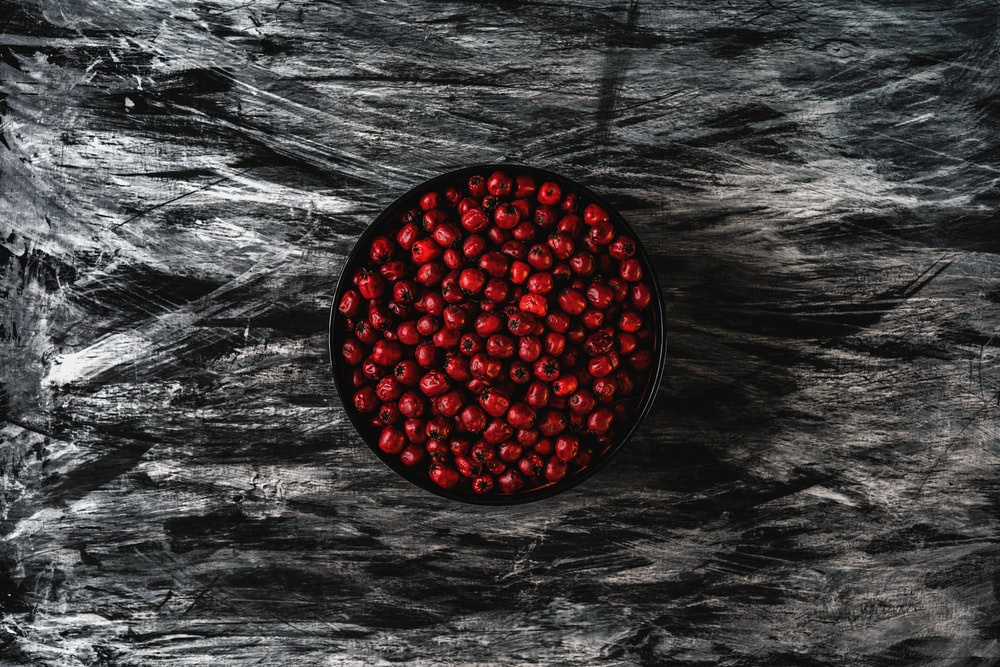 red round fruit on black and white surface