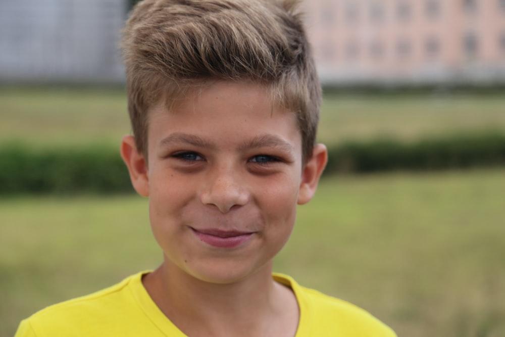 boy in yellow crew neck shirt smiling