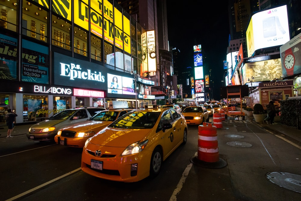 yellow taxi cab on road during night time