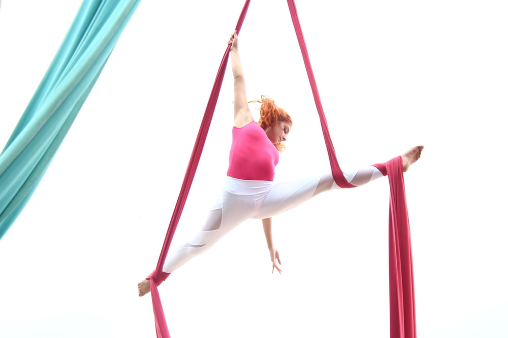 woman in pink tank top and white pants hanging on red hammock