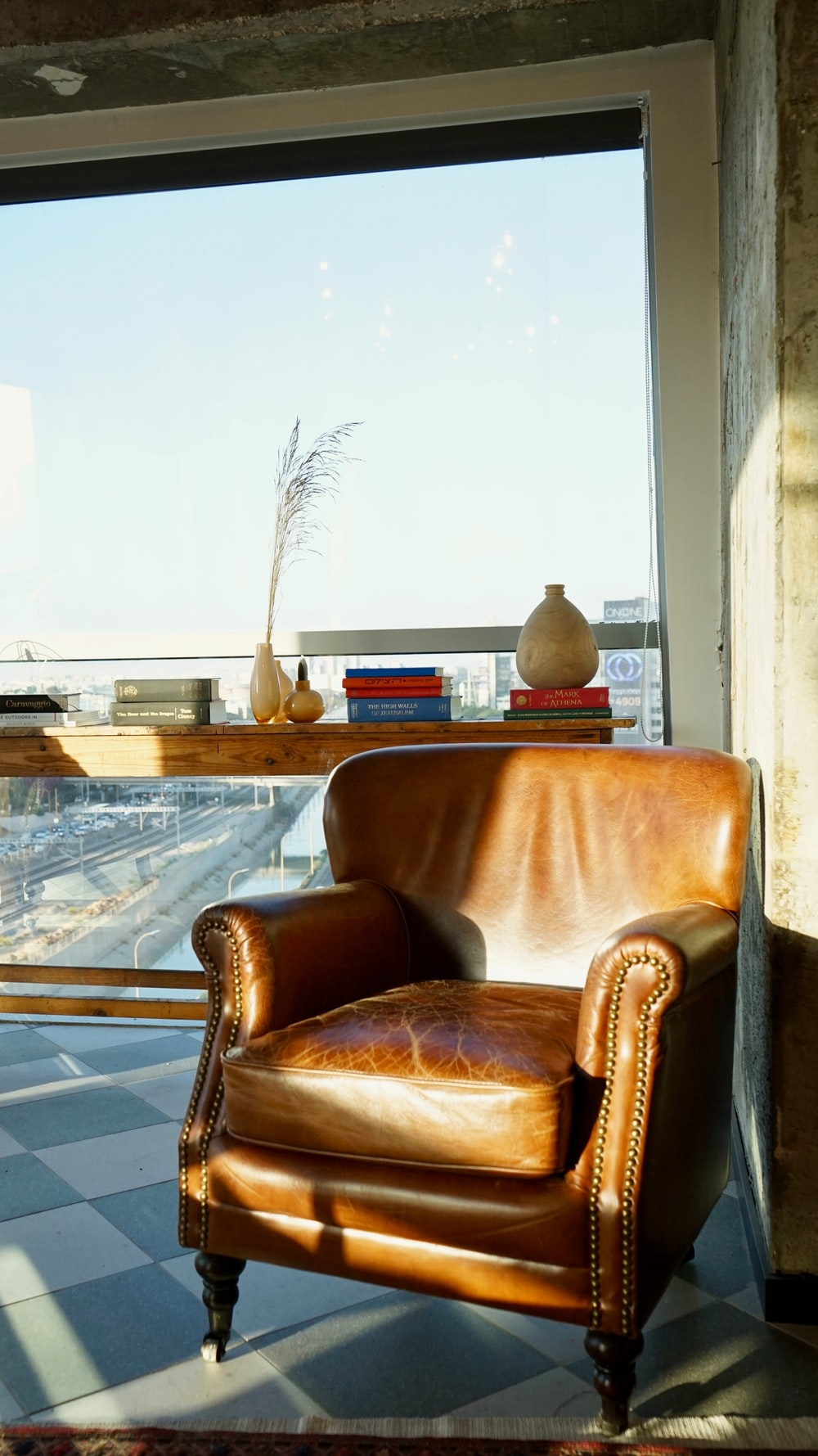 brown leather armchair beside glass table