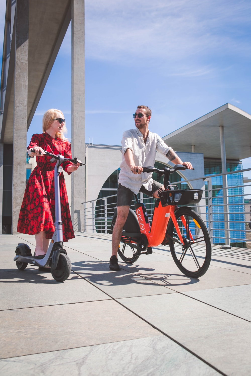 man in white dress shirt and woman in red dress riding on red and black trike