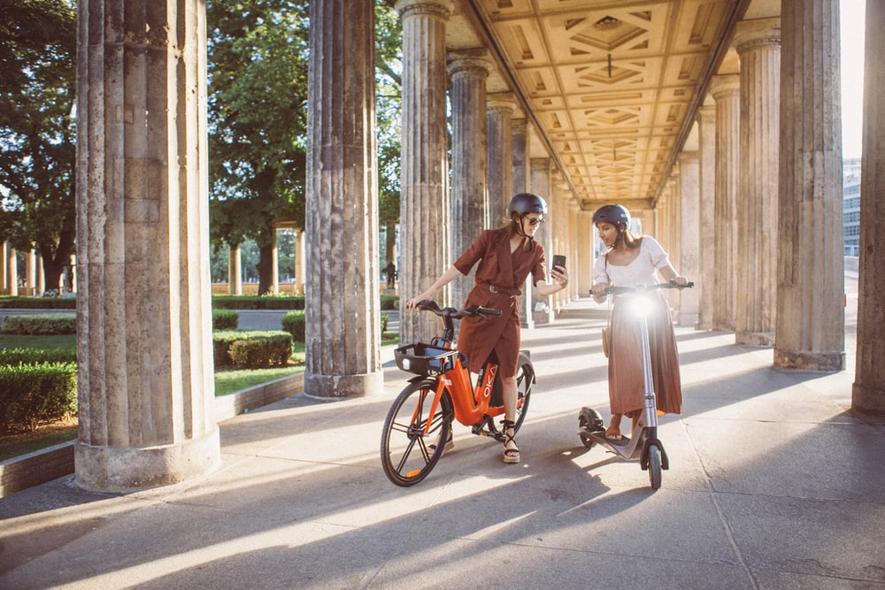 man and woman riding on orange bicycle on road during daytime