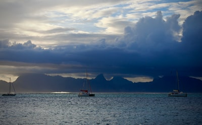 white boat on sea under cloudy sky during daytime tahiti teams background