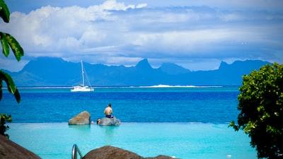 white sail boat on sea during daytime tahiti teams background