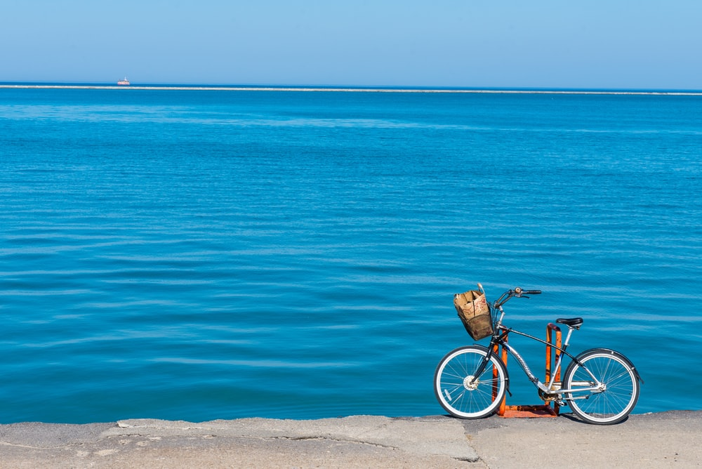 black and white bicycle on brown sand near blue sea during daytime