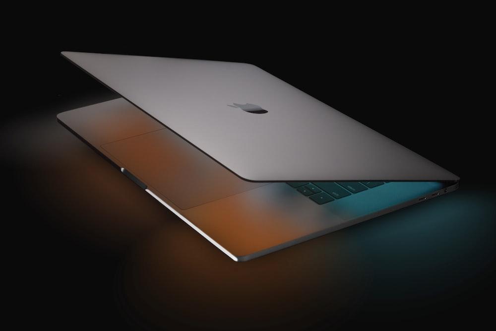 silver macbook on black table