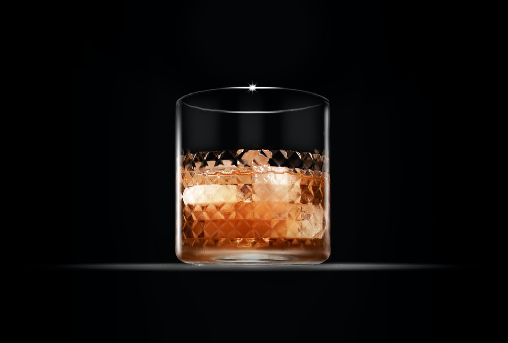 clear drinking glass with brown liquid