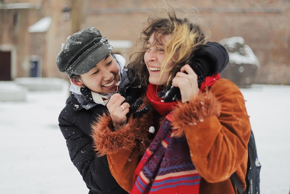woman in black jacket carrying girl in orange jacket