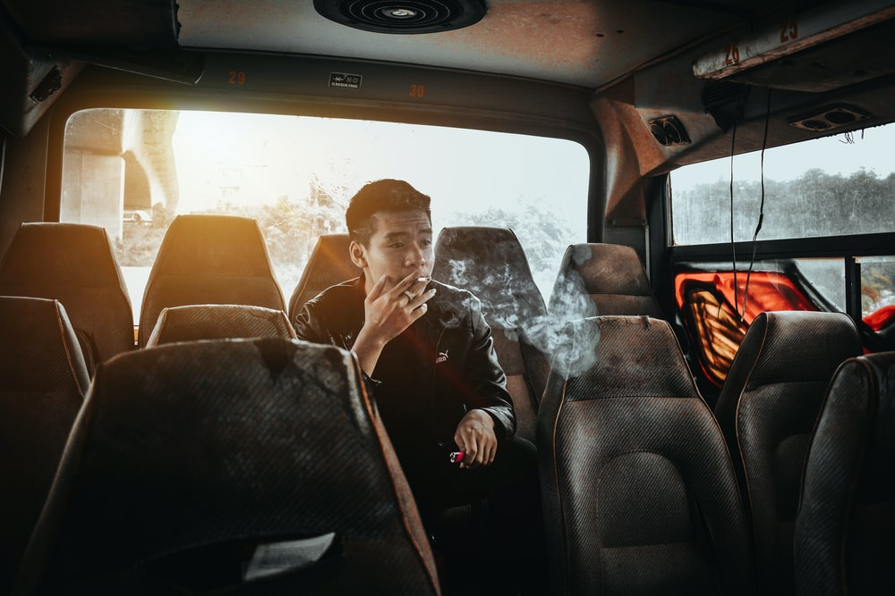 man in black leather jacket sitting on car seat