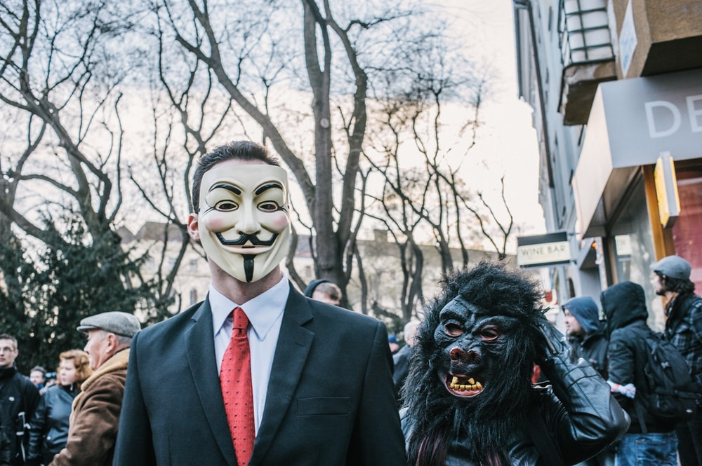 man in black suit jacket wearing black and white mask