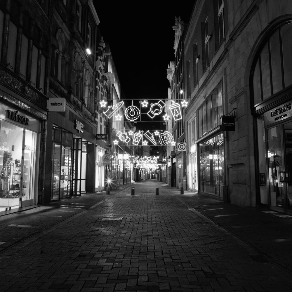 grayscale photo of a street with lighted signage