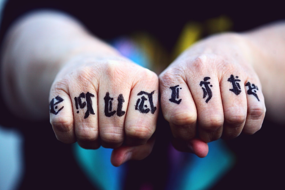 persons hand with black tattoo