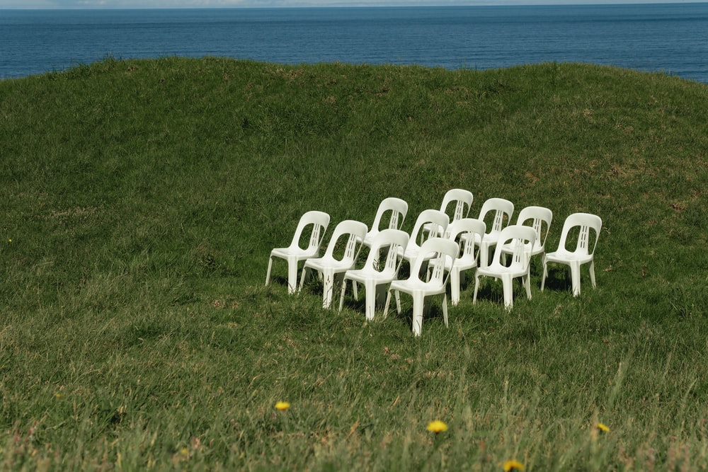 white plastic chairs on green grass field