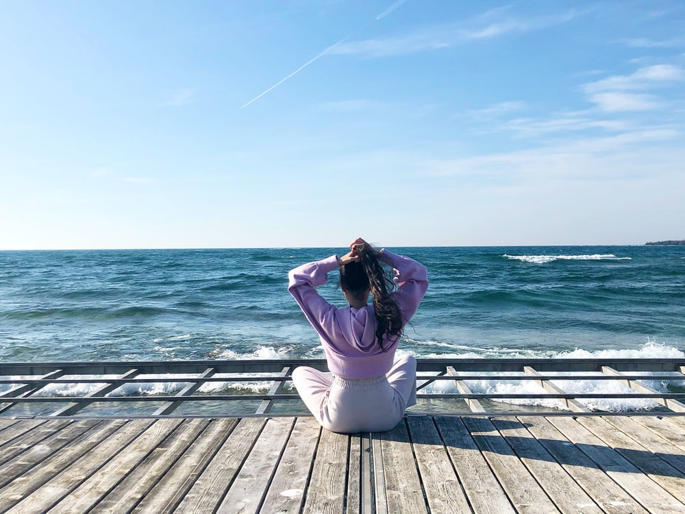 woman in white pants sitting on wooden dock during daytime