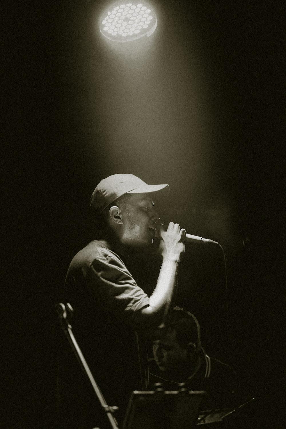 man in black hat singing