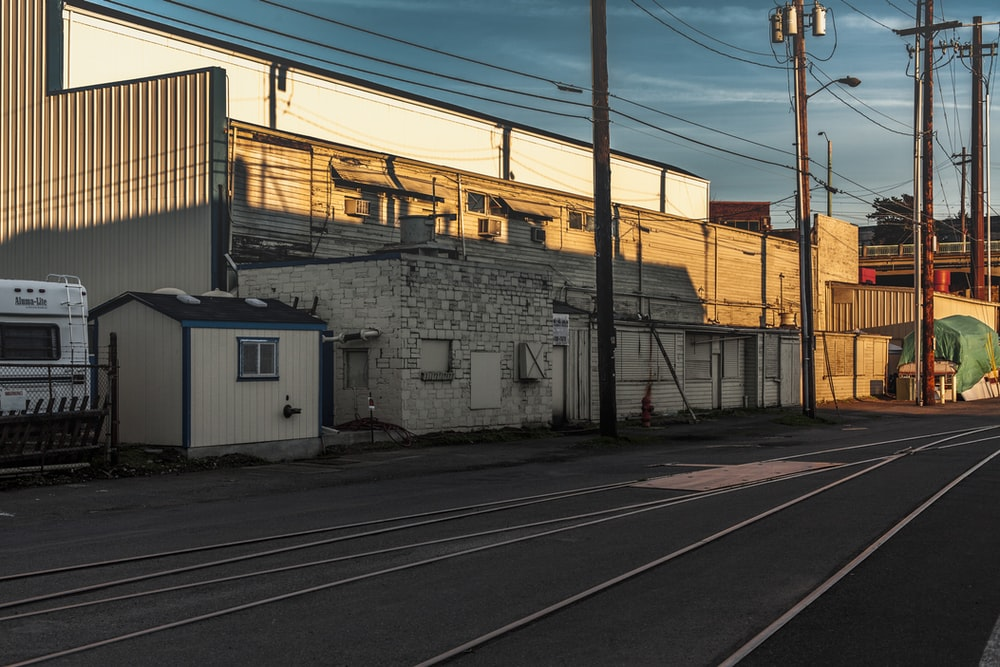 white and gray concrete building beside train rail during daytime