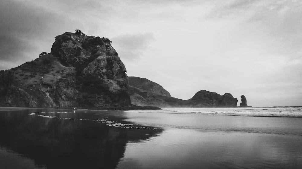 grayscale photo of rocky mountain near body of water