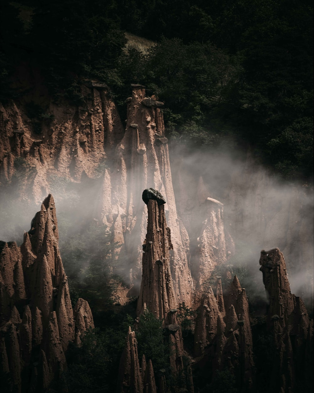 man standing on rock formation in front of waterfalls