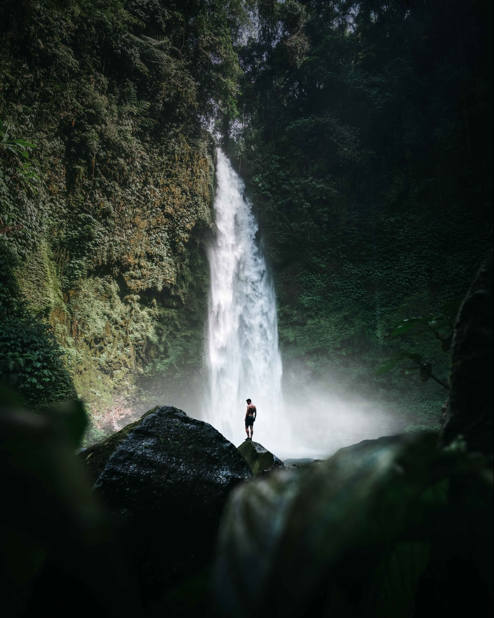 person standing on rock near waterfalls during daytime
