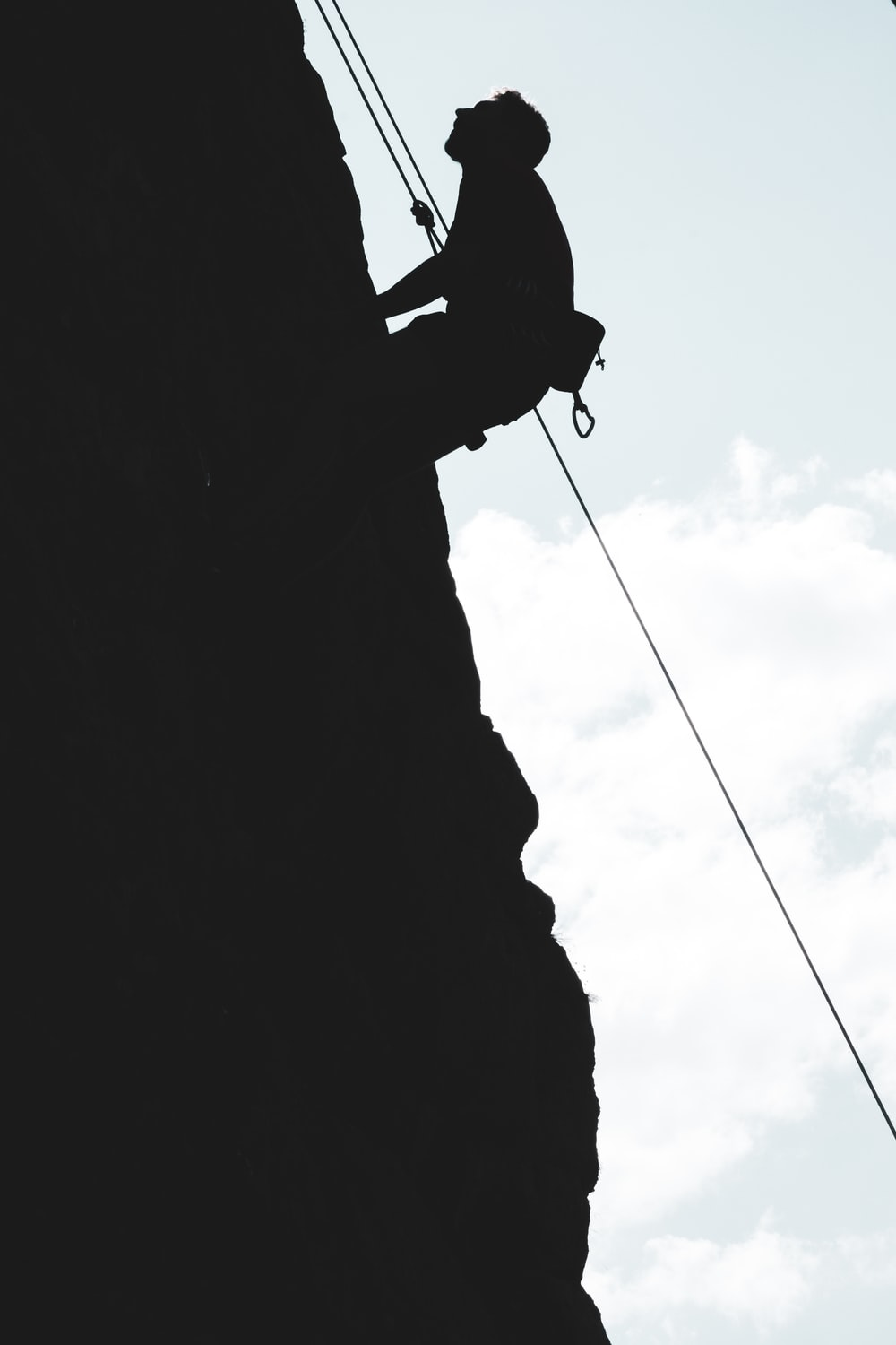 silhouette of man climbing on mountain during daytime
