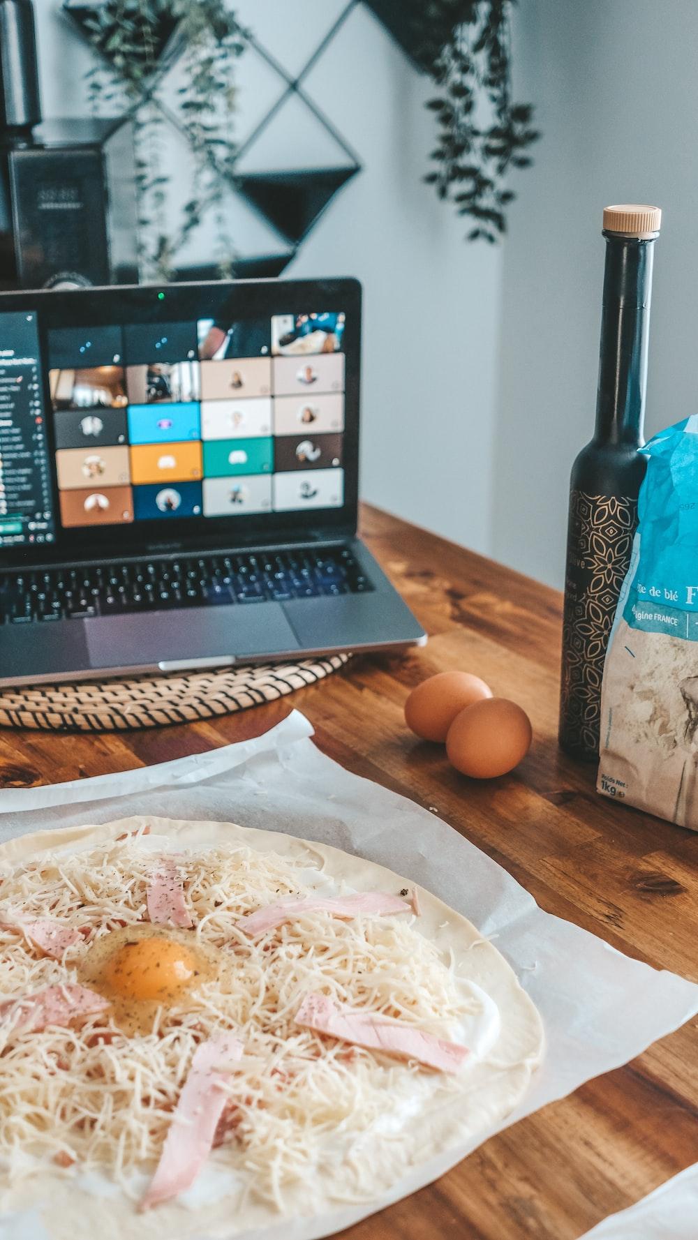 black laptop computer beside brown egg on white paper