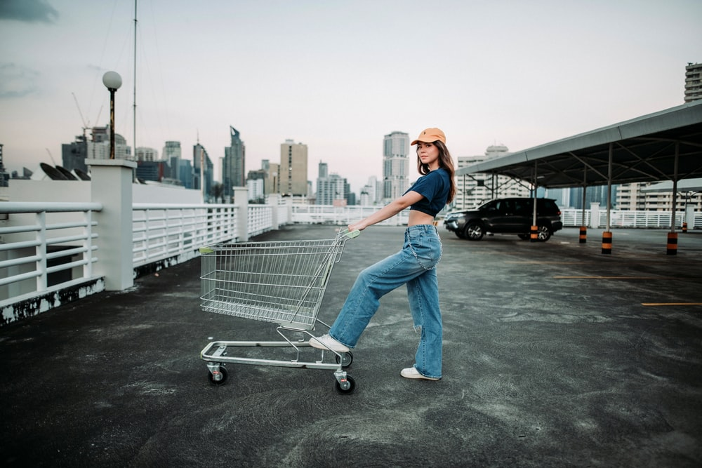 woman in blue denim jeans and white cap standing on gray shopping cart during daytime